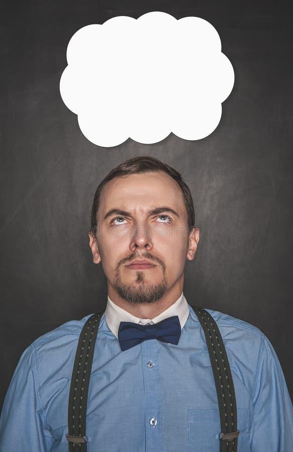 Hombre de negocios o profesor pensativo que mira para arriba en la pizarra imagen de archivo