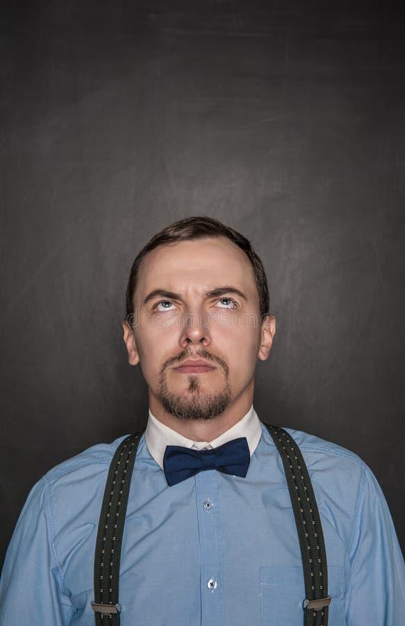 Hombre de negocios o profesor pensativo que mira para arriba en la pizarra fotografía de archivo libre de regalías