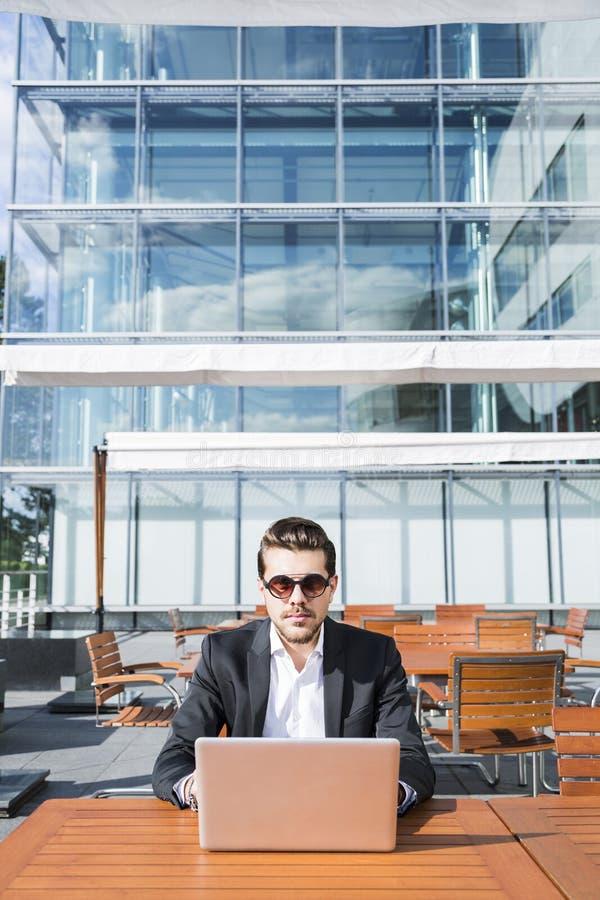 Hombre de negocios o trabajador en traje negro en la tabla y trabajo masculinos en el ordenador fotografía de archivo libre de regalías