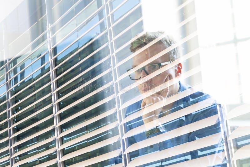 Hombre de negocios ocasional que trabaja en oficina, sentándose en el escritorio, pulsando en el teclado, mirando la pantalla de  imagen de archivo