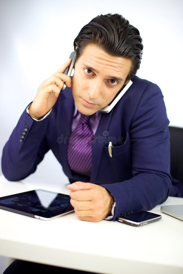 Hombre de negocios ocupado con el teléfono dos que trabaja en el escritorio fotografía de archivo