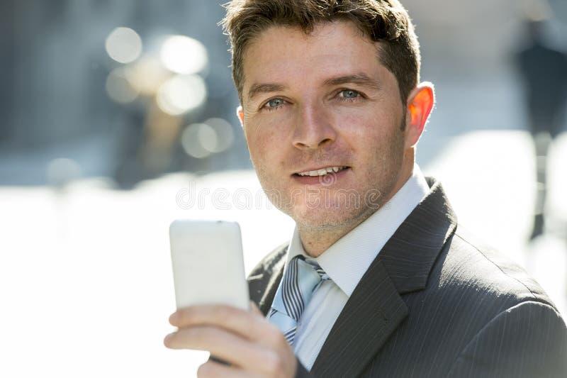 Hombre de negocios ocupado en traje y lazo usando el teléfono móvil que envía el mensaje o que consulta Internet fotos de archivo libres de regalías