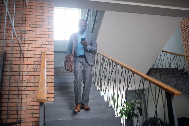 Hombre de negocios ocupado que lleva el mensaje gris de la lectura del traje en el teléfono fotos de archivo libres de regalías