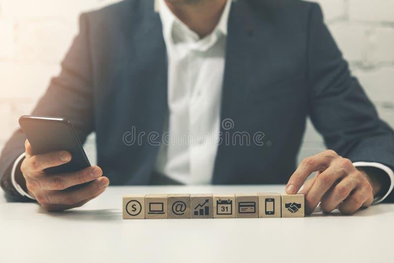 hombre de negocios ocupado que usa smartphone en los trabajos múltiple de la oficina imagen de archivo