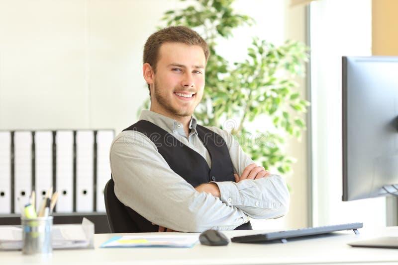 Hombre de negocios orgulloso que presenta en la oficina imagen de archivo