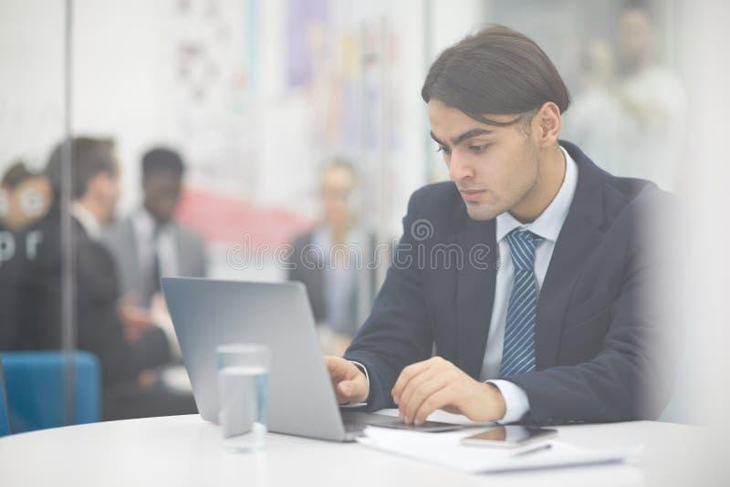 Hombre de negocios de Oriente Medio que usa el ordenador portátil fotografía de archivo libre de regalías