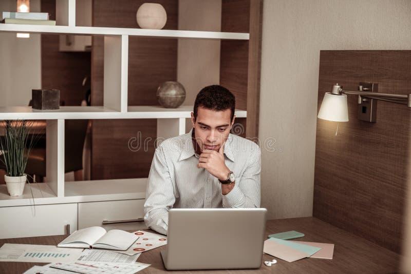 hombre de negocios Oscuro-cabelludo que trabaja en el ordenador portátil que se sienta en la habitación fotos de archivo