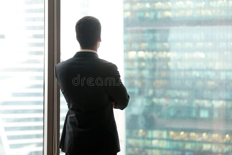 Hombre de negocios pensativo acertado que mira a través de la ventana fotografía de archivo libre de regalías