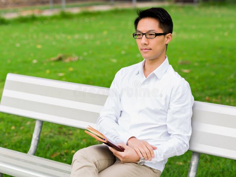 Hombre de negocios pensativo atractivo que se sienta en banco con la libreta imagenes de archivo