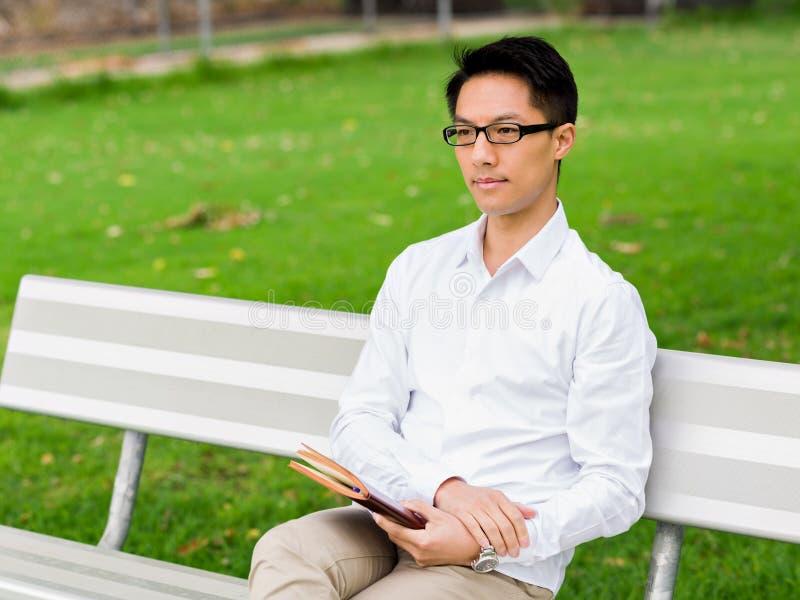 Hombre de negocios pensativo atractivo que se sienta en banco con la libreta fotos de archivo