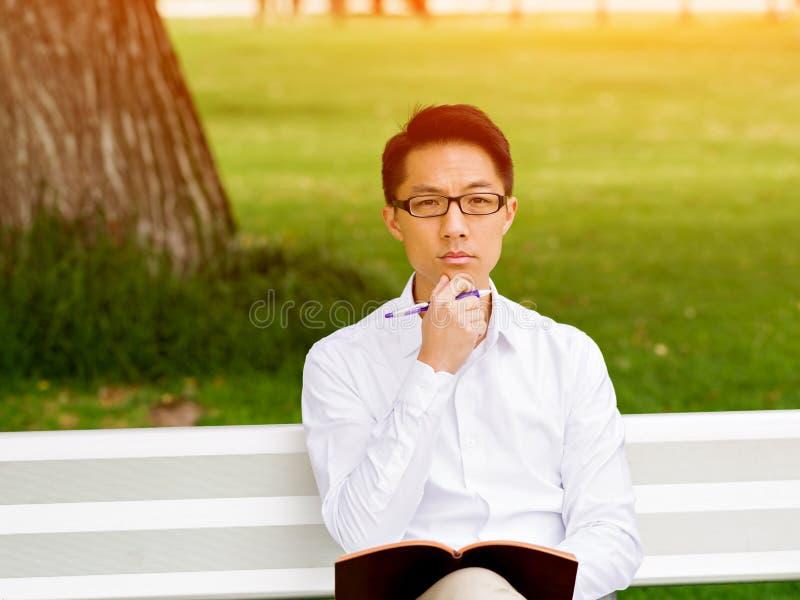 Hombre de negocios pensativo atractivo que se sienta en banco y que escribe en libreta fotos de archivo
