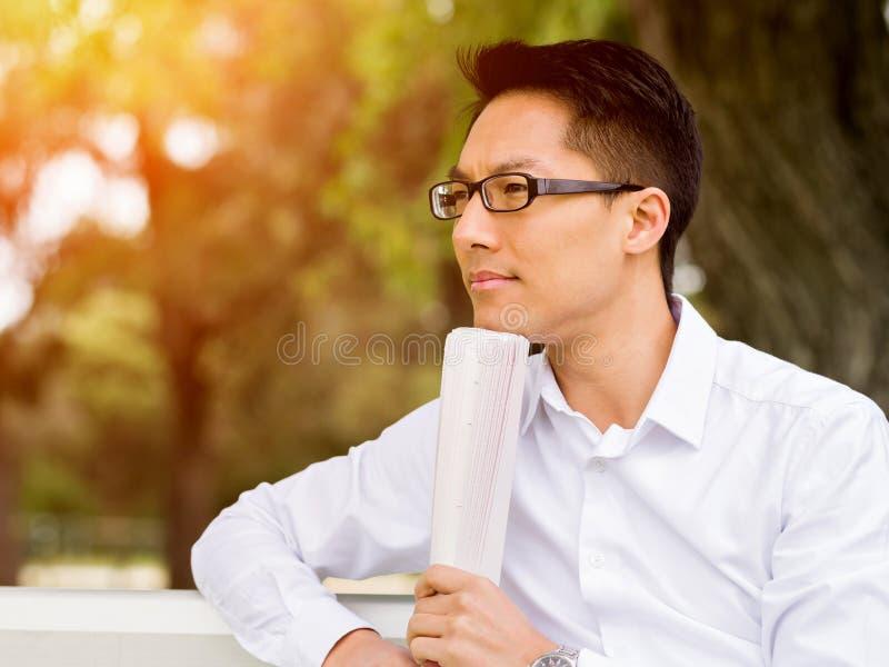 Hombre de negocios pensativo atractivo que se sienta en banco y que escribe en libreta fotografía de archivo