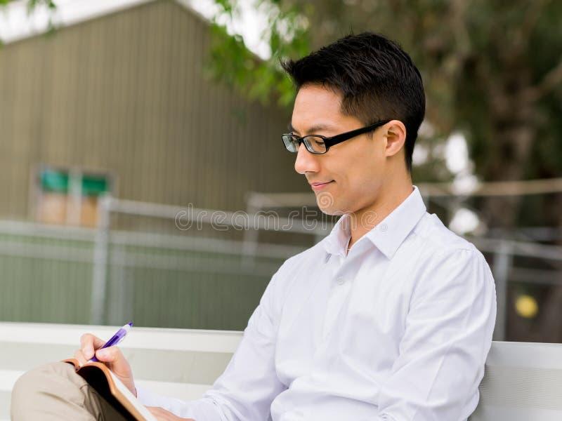 Hombre de negocios pensativo atractivo que se sienta en banco y que escribe en libreta fotografía de archivo libre de regalías