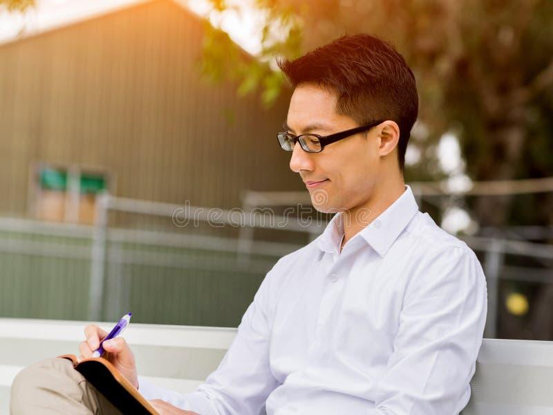 Hombre de negocios pensativo atractivo que se sienta en banco y que escribe en libreta foto de archivo