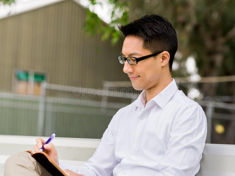 Hombre de negocios pensativo atractivo que se sienta en banco y que escribe en libreta fotos de archivo libres de regalías
