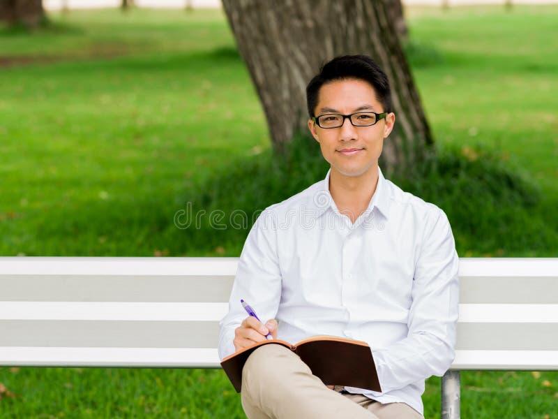 Hombre de negocios pensativo atractivo que se sienta en banco y que escribe en libreta foto de archivo libre de regalías
