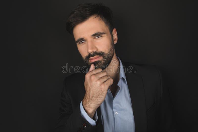 Hombre de negocios pensativo barbudo hermoso que presenta en traje negro imágenes de archivo libres de regalías