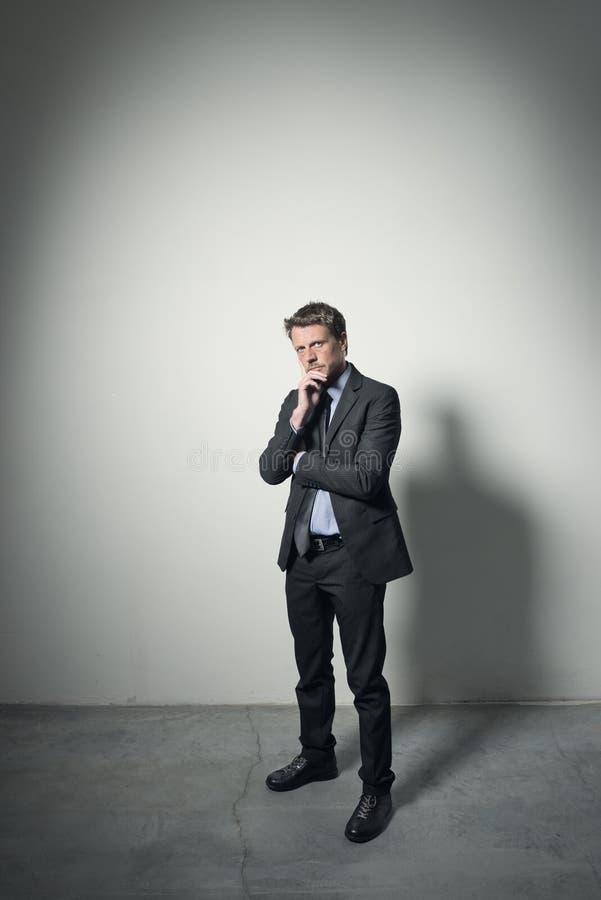 Hombre de negocios pensativo con la mano en la barbilla fotografía de archivo