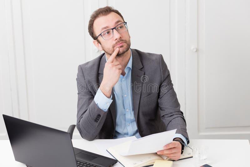 Hombre de negocios pensativo en el escritorio en la oficina imagenes de archivo