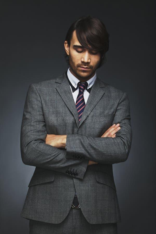 Hombre de negocios pensativo en el traje que se opone a fondo negro imagen de archivo libre de regalías