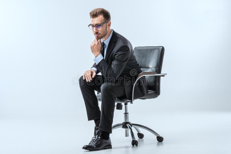 hombre de negocios pensativo en las lentes que se sientan en silla y que miran lejos imagen de archivo