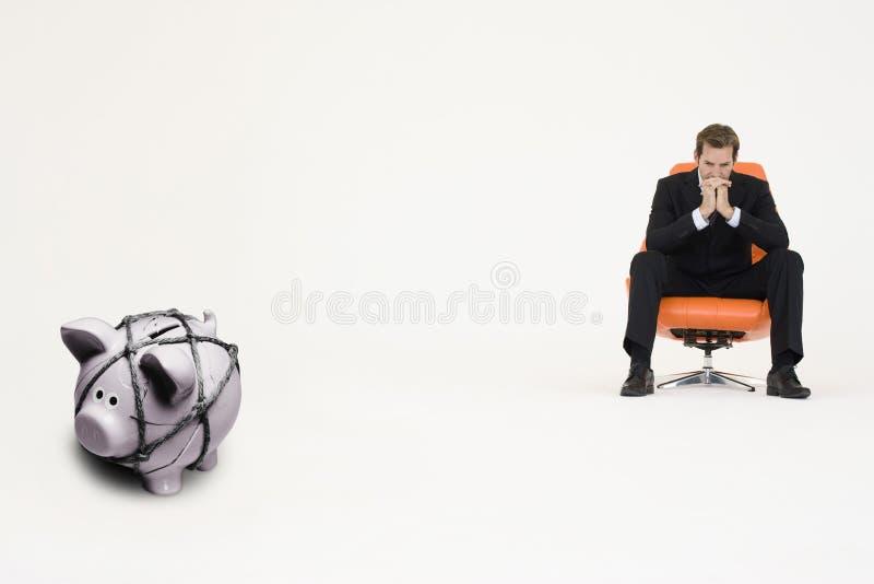 Hombre de negocios pensativo en silla y piggybank atado con la cuerda que representa dificultades financieras fotos de archivo
