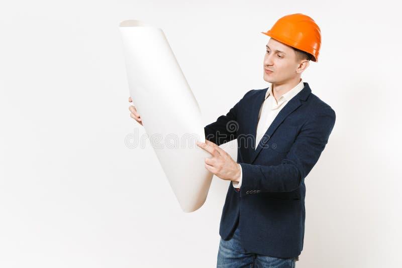 Hombre de negocios pensativo hermoso joven en el traje oscuro, plan del modelo del casco anaranjado protector de la construcción  fotos de archivo libres de regalías