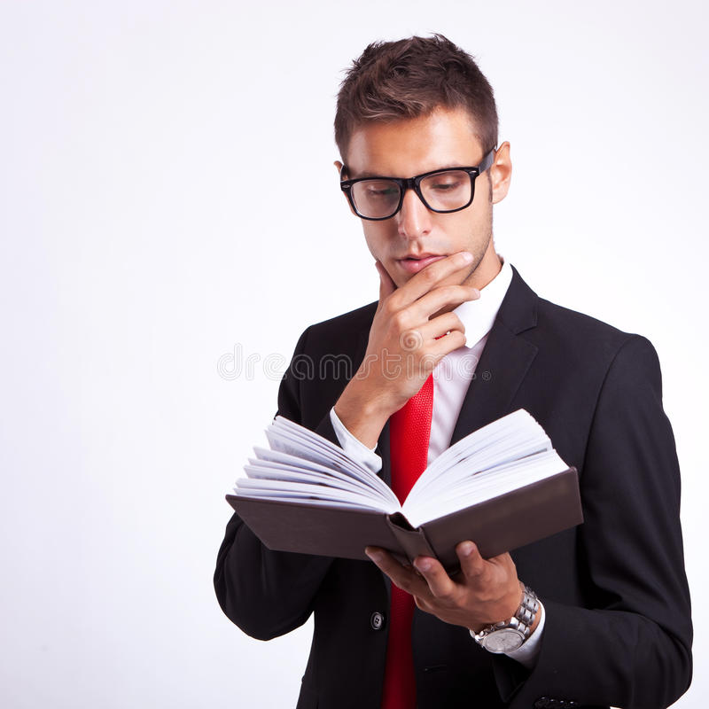 Hombre de negocios pensativo que lee un libro imagenes de archivo