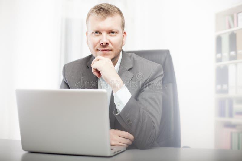 Hombre de negocios pensativo que mira fijamente la cámara foto de archivo