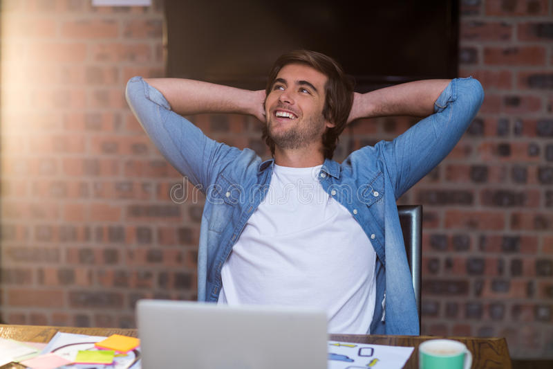 Hombre de negocios pensativo que se relaja en oficina foto de archivo libre de regalías