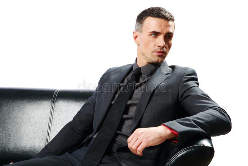 Hombre de negocios pensativo que se sienta en el sofá imagenes de archivo