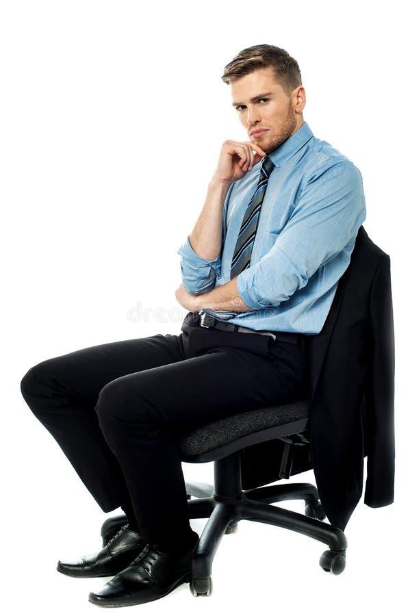 Hombre de negocios pensativo que se sienta en la silla fotografía de archivo