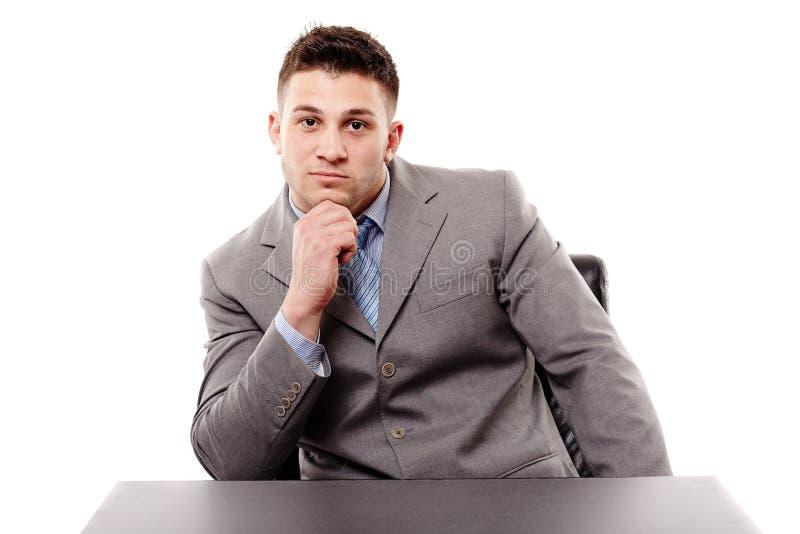 Hombre de negocios pensativo que se sienta en la tabla con la mano en la barbilla fotos de archivo libres de regalías