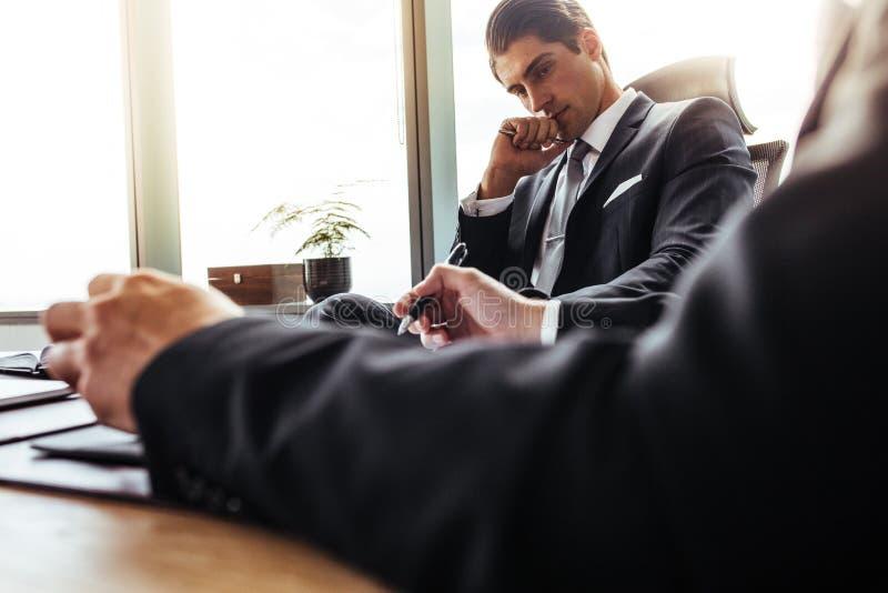 Hombre de negocios pensativo que se sienta en su escritorio con el socio foto de archivo libre de regalías
