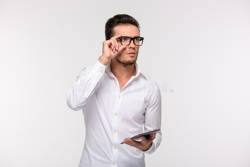 Hombre de negocios pensativo que sostiene la tableta fotos de archivo