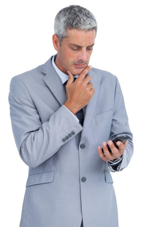 Hombre de negocios pensativo que toca su barbilla y que mira su teléfono fotos de archivo libres de regalías