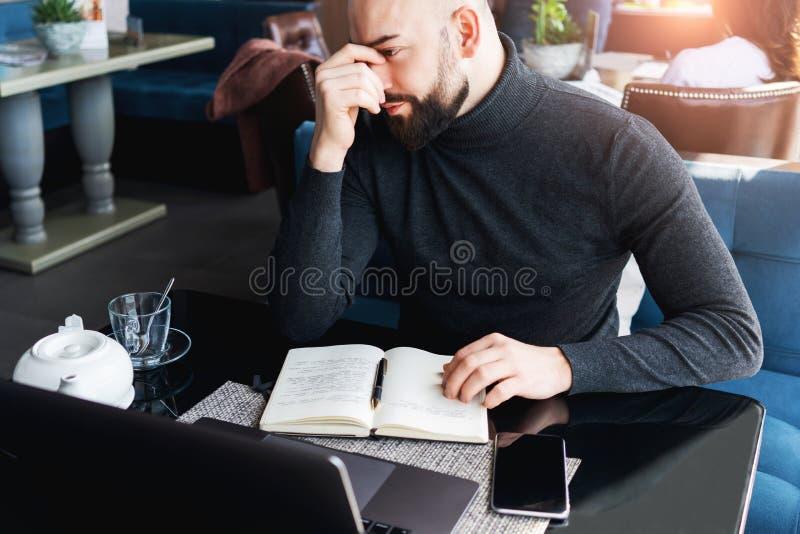 Hombre de negocios pensativo serio que se sienta en café sobre el cuaderno y que trabaja en el ordenador portátil Estudiante mile imagen de archivo libre de regalías