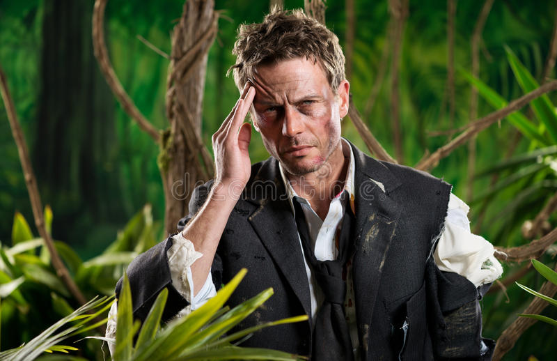 Hombre de negocios perdido en selva con dolor de cabeza fotografía de archivo