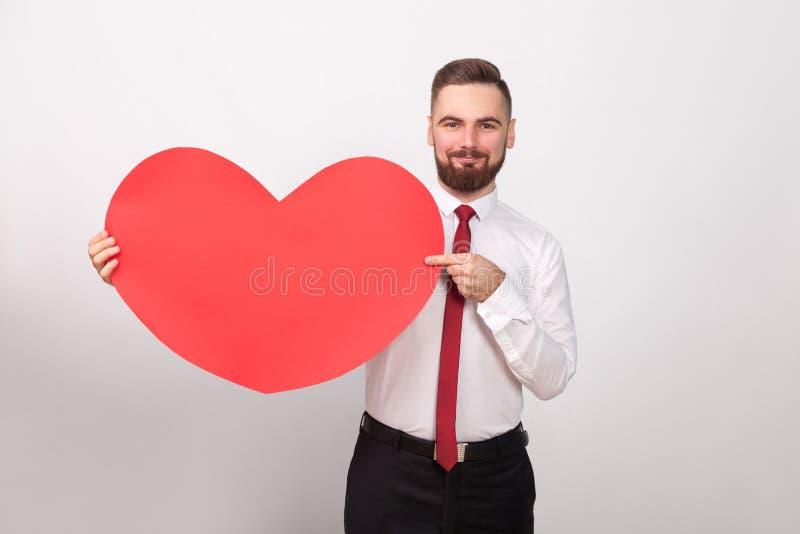 Hombre de negocios perfecto que sonríe, señalando el finger en el corazón rojo grande fotografía de archivo