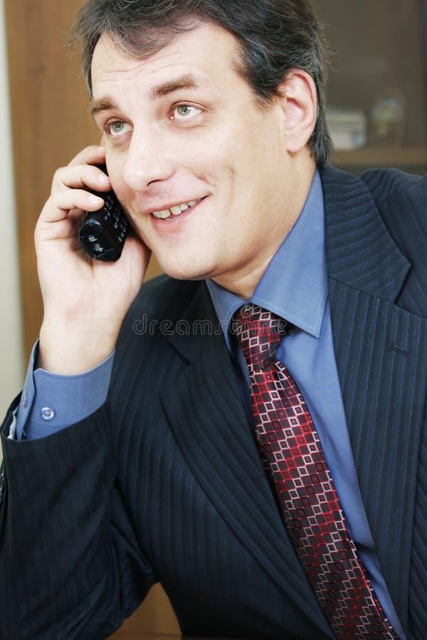 Hombre de negocios positivo que habla vía el teléfono foto de archivo