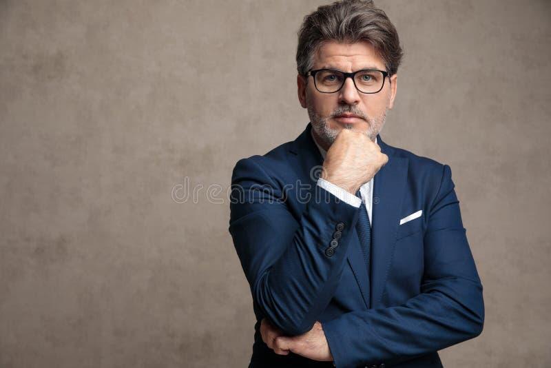 Hombre de negocios potente que se sostiene el brazo en su barbilla imagenes de archivo