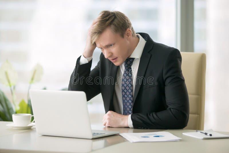 Hombre de negocios preocupado con el ordenador portátil foto de archivo libre de regalías