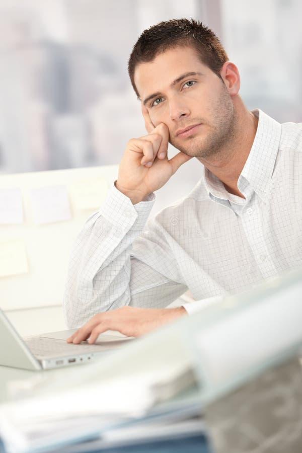 Hombre de negocios preocupado que se sienta en el escritorio imagen de archivo