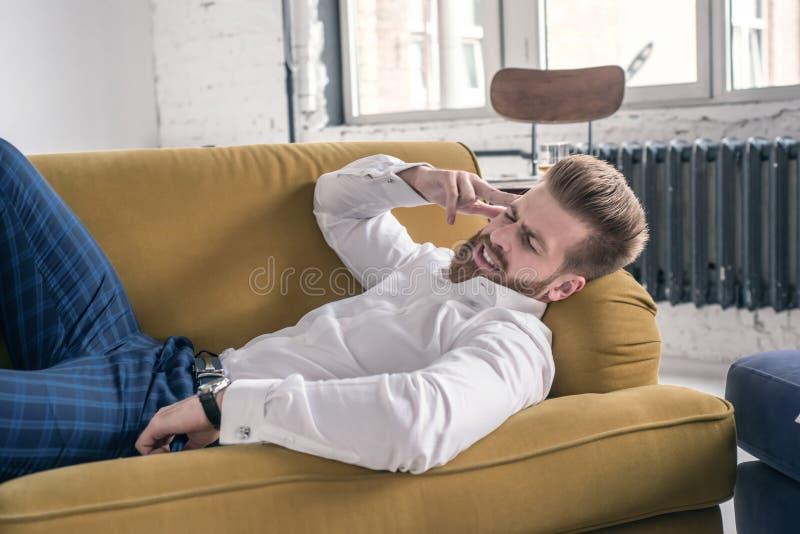 Hombre de negocios preocupante con el dolor de cabeza que miente en el sofá en sala de estar imagen de archivo