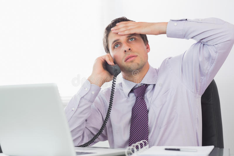 Hombre de negocios preocupante en llamada en el escritorio imagenes de archivo
