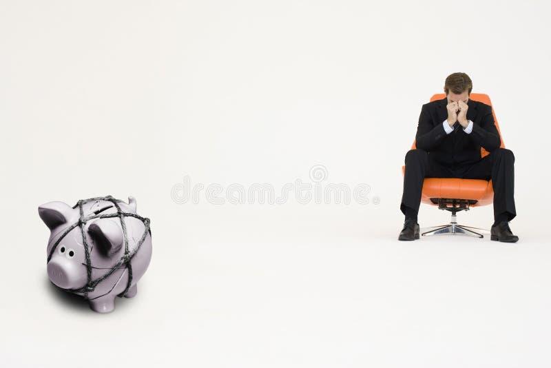 Hombre de negocios preocupante en silla y piggybank atado con la cuerda que representa dificultades financieras fotografía de archivo libre de regalías