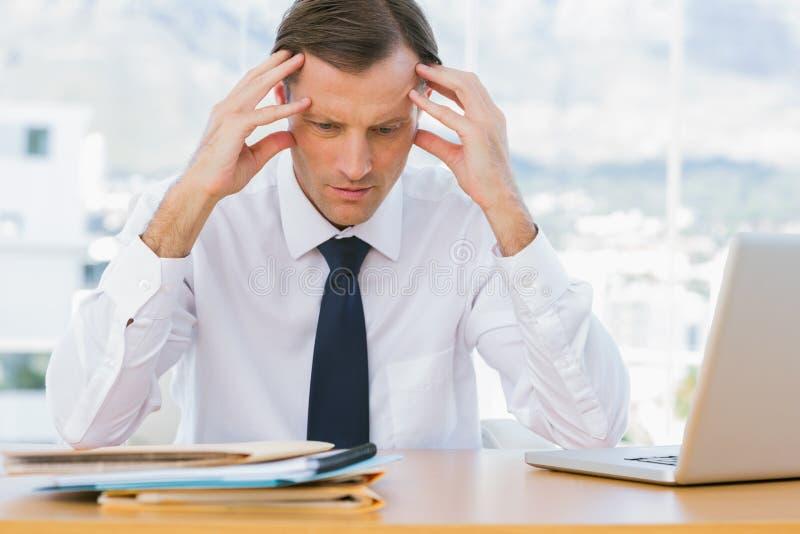 Hombre de negocios preocupante que lleva a cabo su cabeza fotos de archivo