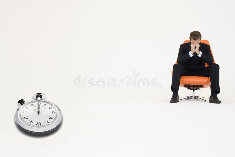 Hombre de negocios preocupante que se sienta en silla con el cronómetro que representa la pérdida de tiempo imagen de archivo