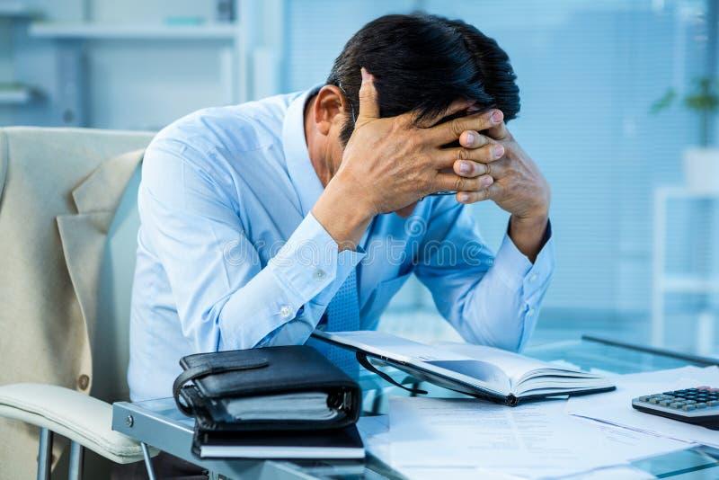 Hombre de negocios preocupante que trabaja en su escritorio foto de archivo