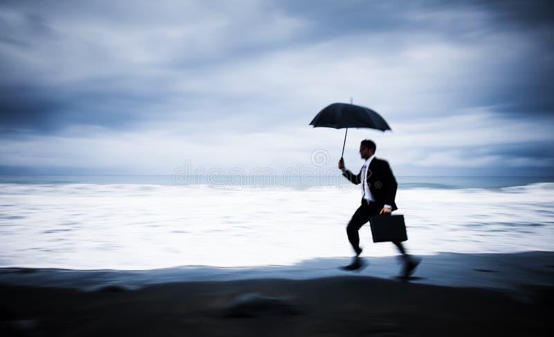 Hombre de negocios preocupante Running por la playa foto de archivo